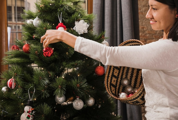 Mulher sorrindo enquanto decorava a árvore de natal Foto gratuita