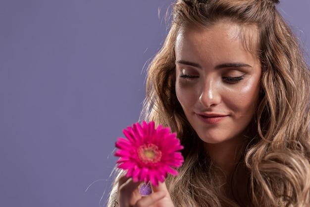 Mulher sorrindo enquanto segura um crisântemo com espaço de cópia Foto gratuita