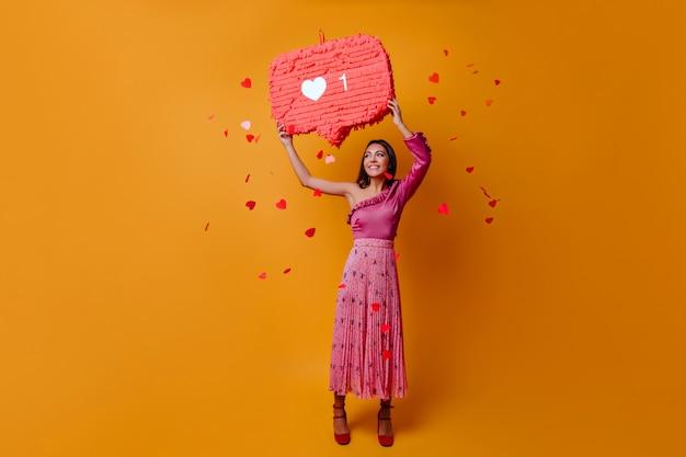 Mulher sortuda e charmosa de 23 anos segurando um cartaz em forma de like do instagram e posando em tamanho natural na parede laranja com confete Foto gratuita