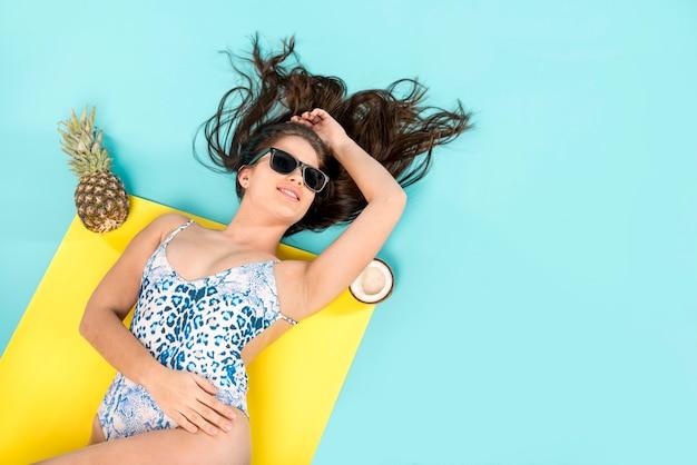 Mulher, sunbathing, ligado, toalha, com, fruta Foto Premium