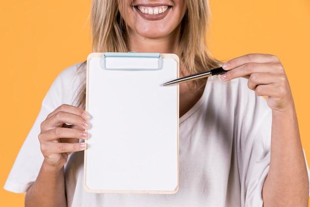 Mulher surda mostrando algo no papel branco em branco com a área de transferência Foto gratuita