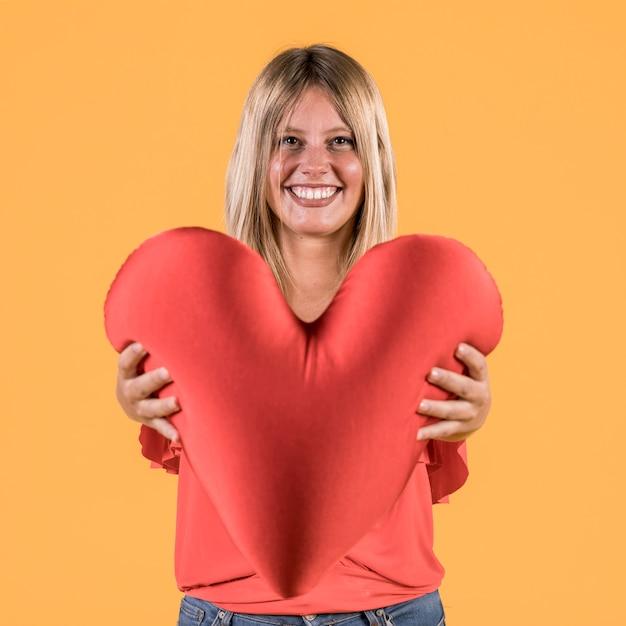Mulher surda sorridente dando almofada de forma de coração vermelho para alguém Foto gratuita