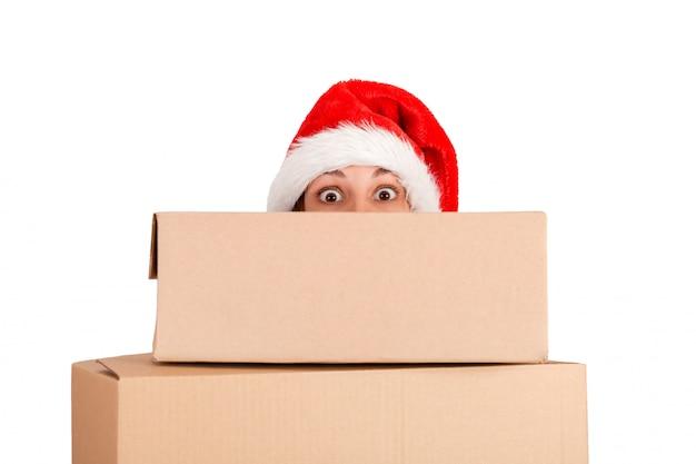 Mulher surpreendida no chapéu do natal que guarda o presente de natal na frente. isolado Foto Premium
