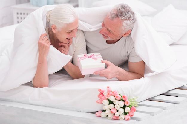 Mulher surpreendida olhando para caixa de presente, dada pelo marido na cama Foto gratuita