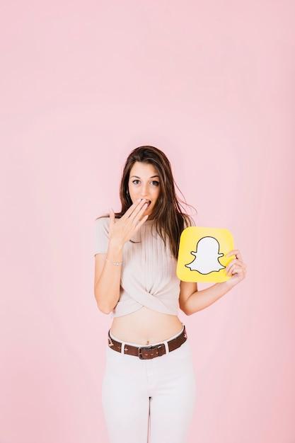 Mulher surpreendida segurando o ícone do snapchat em fundo rosa Foto gratuita