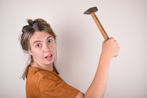 Mulher surpreendida segurando um martelo nas mãos, que não sabe como fazer reparos na casa. mulher com um martelo fica surpresa com a pergunta. o conceito da escolha dos materiais de construção Foto Premium
