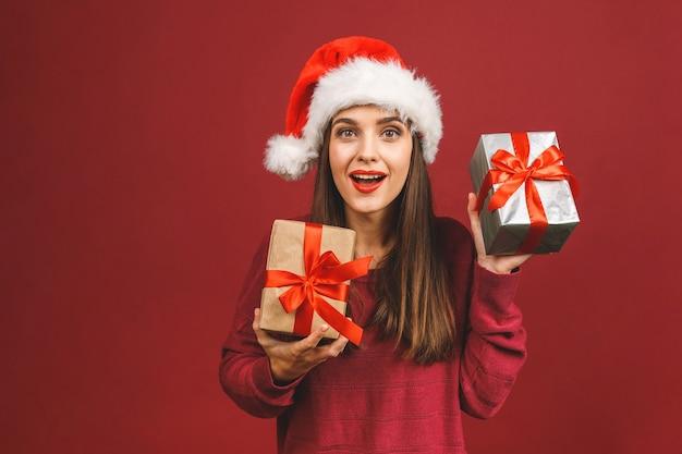 Mulher surpresa e animada com roupa vermelha de papai noel segurando um presente Foto Premium