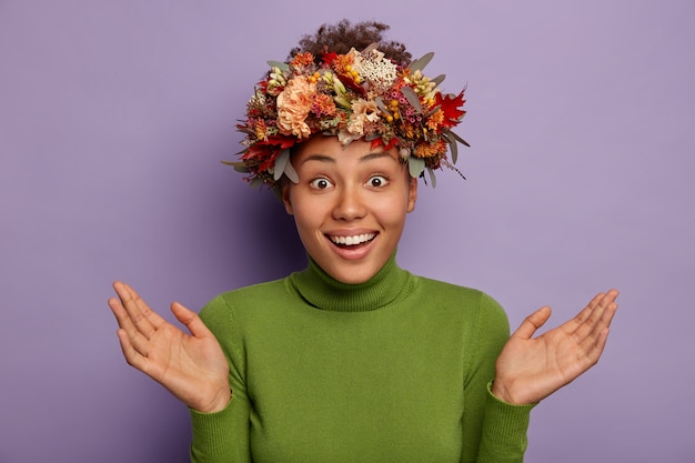 Mulher surpresa feliz e inconsciente espalha as palmas das mãos, sorri alegremente, mostra dentes brancos, usa guirlanda de outono feita à mão e gola verde, isolada sobre fundo roxo Foto gratuita