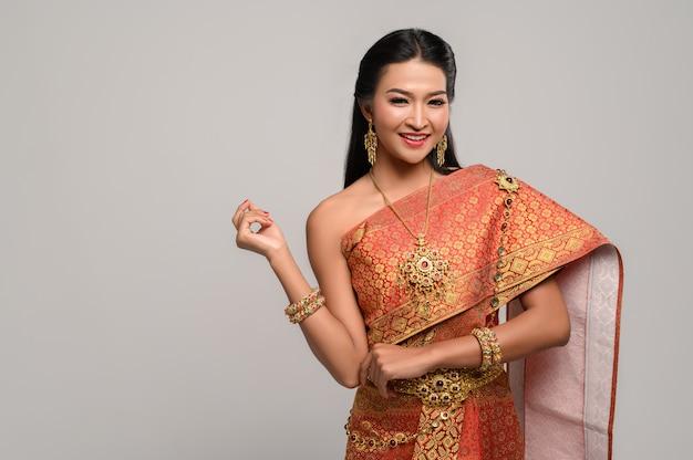 Mulher tailandesa bonita que veste um vestido tailandês e um sorriso feliz. Foto gratuita