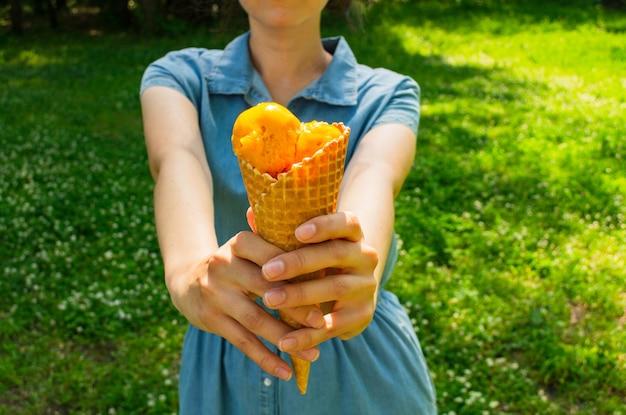 Mulher tem um sorvete nas mãos dela. sorvete de manga em um cone de waffle Foto Premium