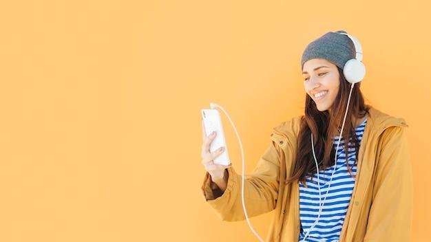 Mulher, tendo, chamada vídeo, ligado, cellphone, com, headset, contra, amarela, superfície Foto gratuita