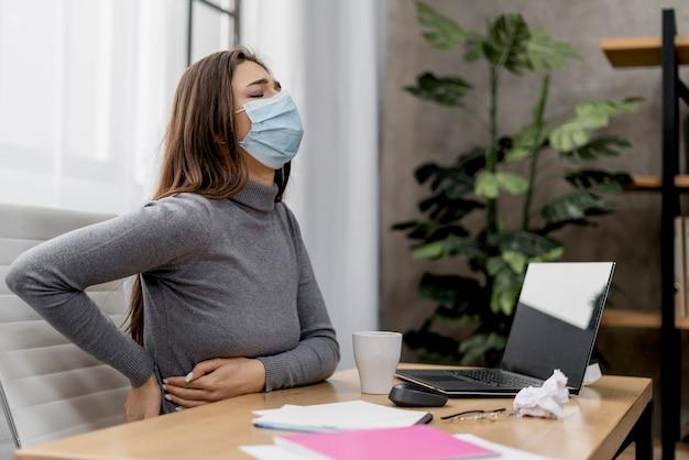 Mulher tendo dor nas costas enquanto trabalha em casa Foto gratuita