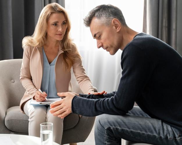Mulher terapeuta confortando paciente Foto gratuita
