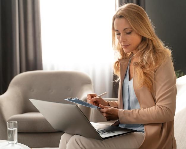Mulher terapeuta fazendo anotações com o laptop no colo Foto gratuita
