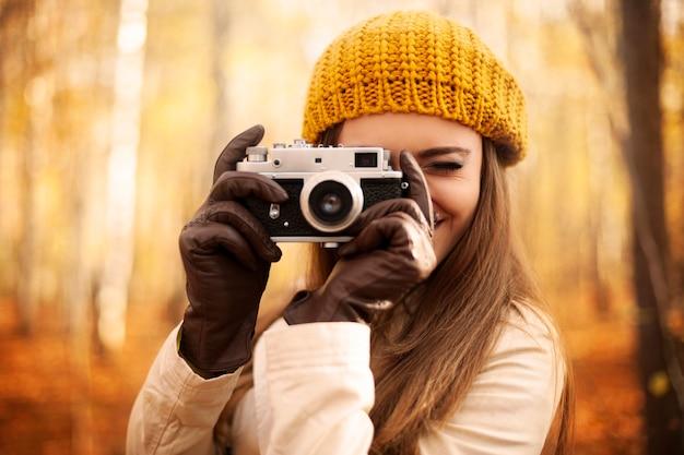 Mulher tirando foto com câmera retro Foto gratuita