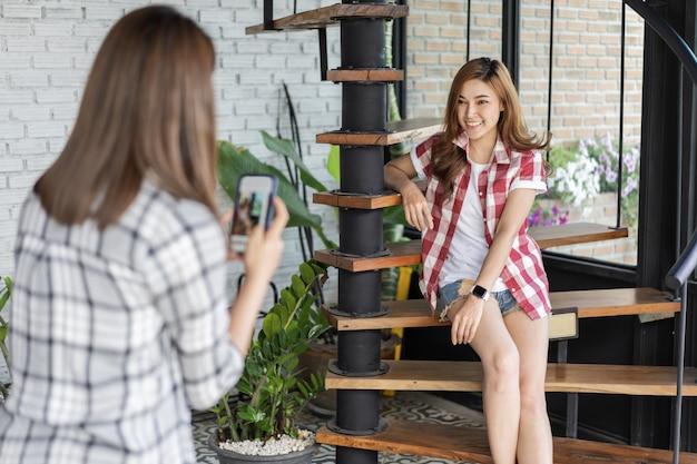 Mulher tirando foto de sua amiga com smartphone no café Foto Premium