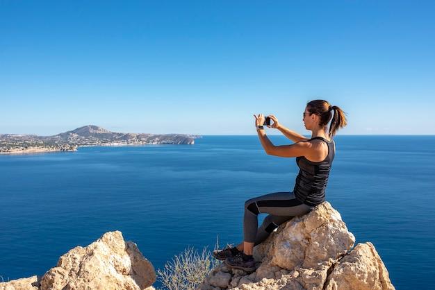 Mulher tirando fotos com seu smartphone para a paisagem, na natureza do peñon de ifach em calpe Foto Premium