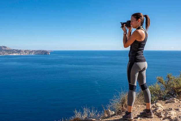 Mulher tirando fotos com sua câmera para a paisagem, na natureza do peñon de ifach em calpe Foto Premium