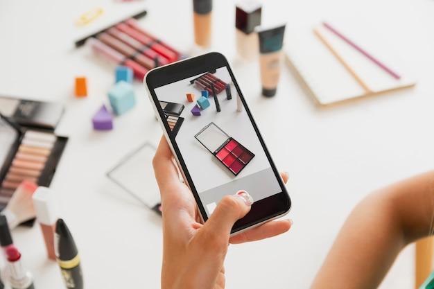 Mulher tirando fotos de produtos de maquiagem Foto gratuita