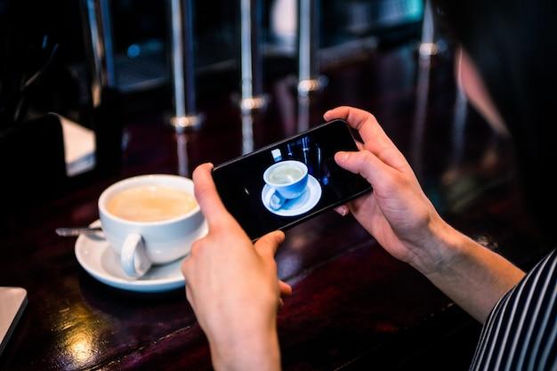 Mulher tirando uma foto de café com smartphone em um café Foto Premium