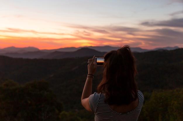Mulher tirando uma foto de uma bela paisagem natural Foto gratuita