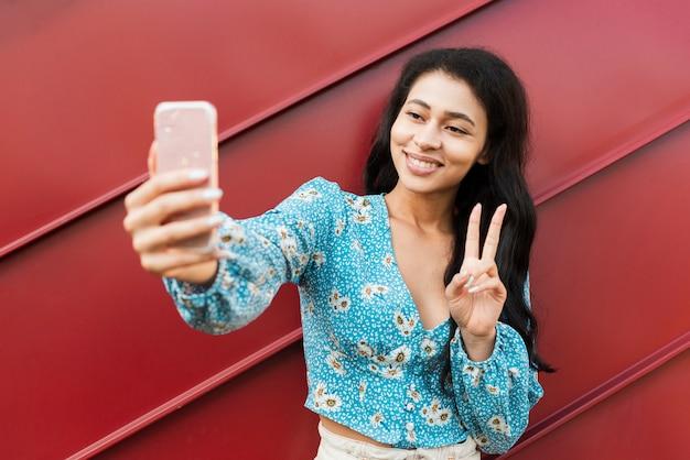 Mulher tirando uma foto do auto e mostrando sinal de paz Foto gratuita