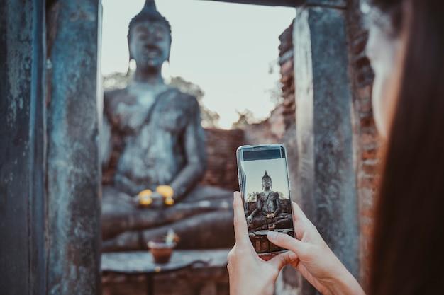 Mulher tirando uma foto horizontal com o telefone de tela em sentado buddha em wat mahathat no parque nacional de sukhothai. Foto Premium