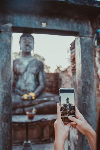 Mulher tirando uma foto vertical com o telefone de tela em sentado buddha em wat mahathat no parque nacional de sukhothai. Foto Premium