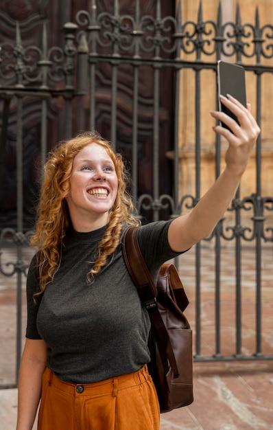Mulher tirando uma selfie na frente do prédio Foto Premium