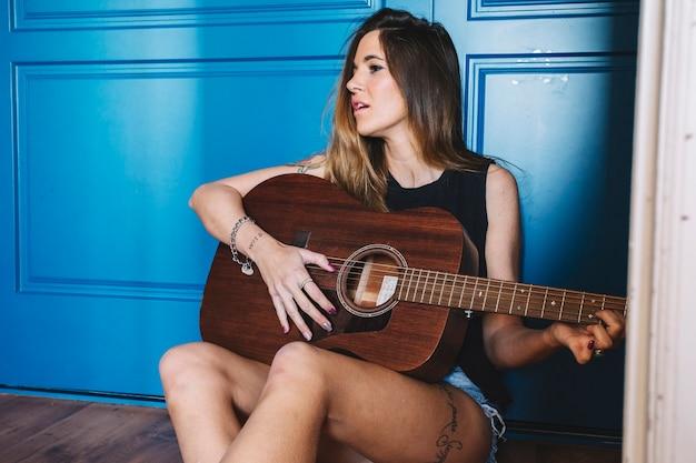 Mulher tocando guitarra perto da parede azul Foto gratuita
