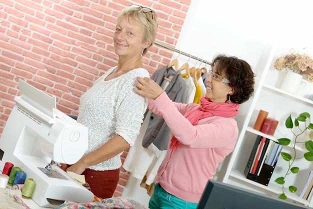 Mulher toma medidas no cliente com fita métrica Foto Premium