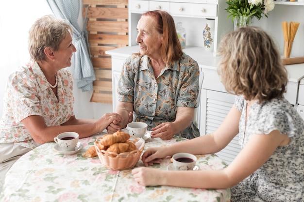 Mulher tomando café da manhã com a mãe e a avó em casa Foto gratuita