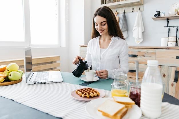 Mulher tomando café da manhã na cozinha Foto gratuita