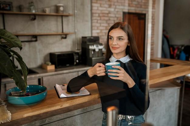 Mulher tomando café durante uma reunião Foto gratuita