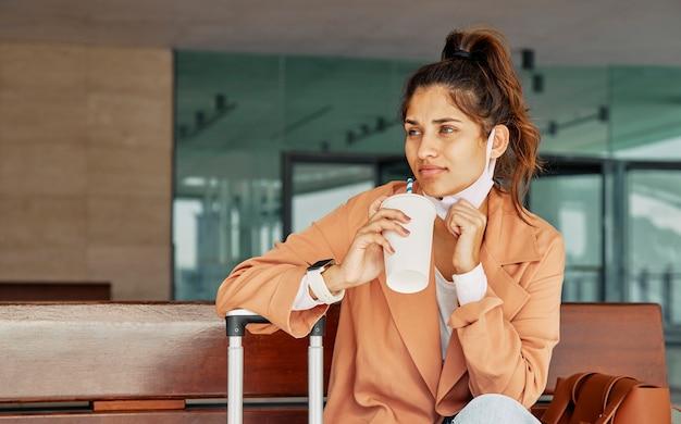 Mulher tomando café no aeroporto durante a pandemia Foto gratuita