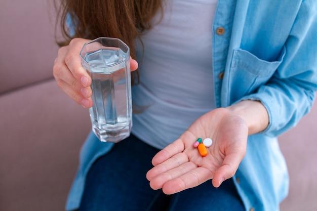 Mulher tomando pílulas e vitaminas para o bem-estar. cuidados de saúde e tratamento de doenças. Foto Premium
