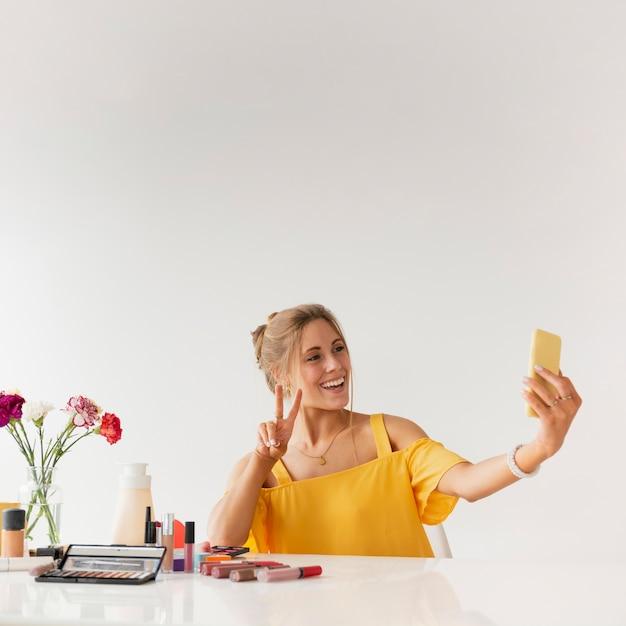 Mulher tomando selfie ao mostrar sinal de paz Foto gratuita
