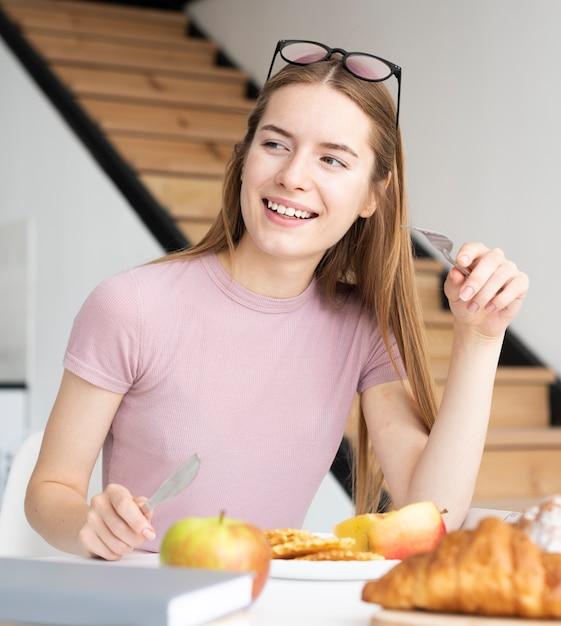 Mulher tomando um delicioso café da manhã Foto gratuita