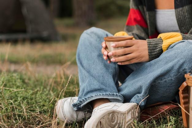 Mulher tomando uma bebida quente enquanto acampa Foto Premium