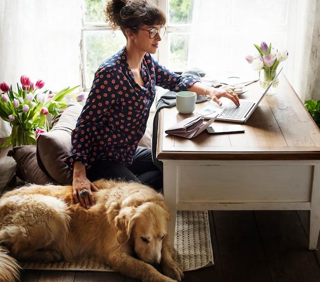 Mulher, trabalhando casa, com, dela, cão Foto Premium