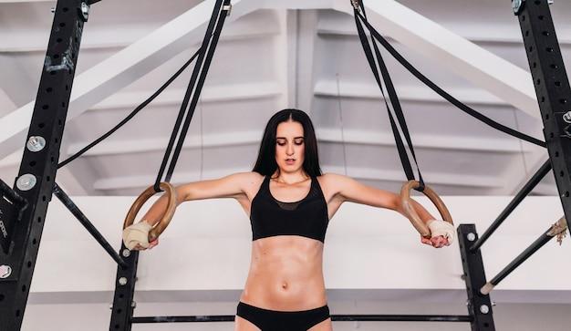Mulher trabalhando com anéis de ginástica na academia cross fit Foto gratuita