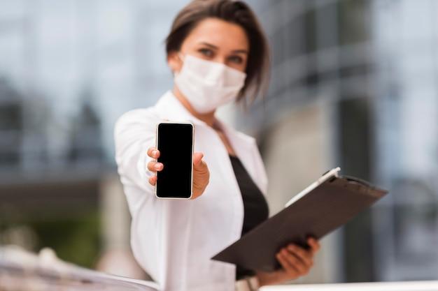 Mulher trabalhando durante a pandemia ao ar livre mostrando smartphone enquanto segura o bloco de notas Foto gratuita