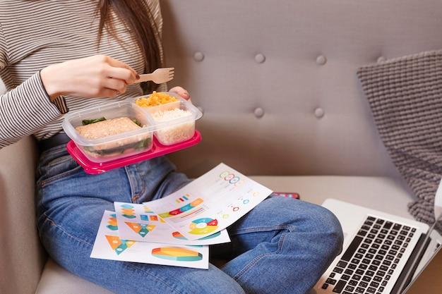 Mulher trabalhando e comendo em um sofá Foto gratuita