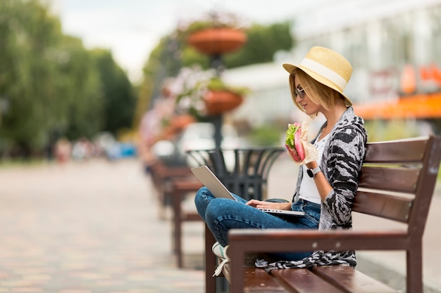 Mulher, trabalhando, e, comer, ligado, banco Foto gratuita