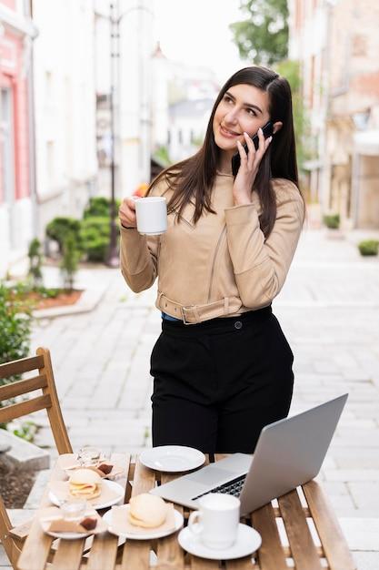 Mulher trabalhando e tomando café ao ar livre Foto gratuita