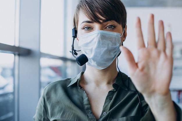 Mulher trabalhando em estúdio de gravação usando máscara Foto gratuita