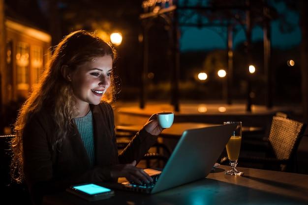 Mulher trabalhando no laptop e bebendo café à noite. imagem iso alta. Foto Premium