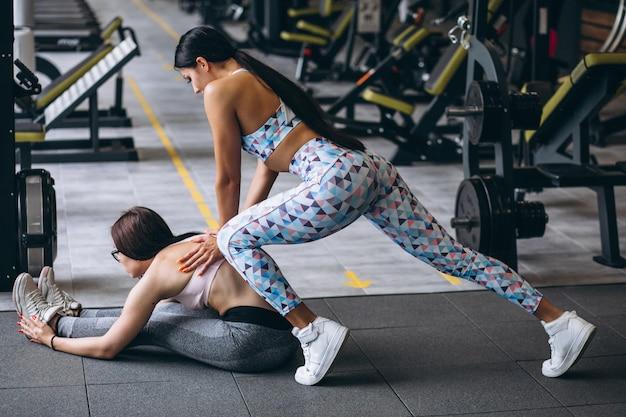 Mulher treinando na academia com instrutor de fitness feminino Foto gratuita
