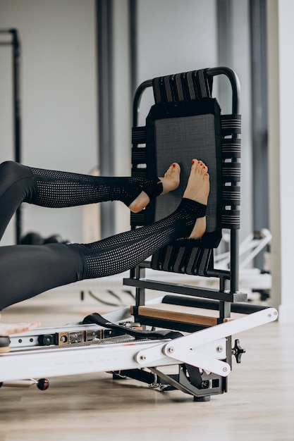 Mulher treinando pilates no reformador Foto gratuita