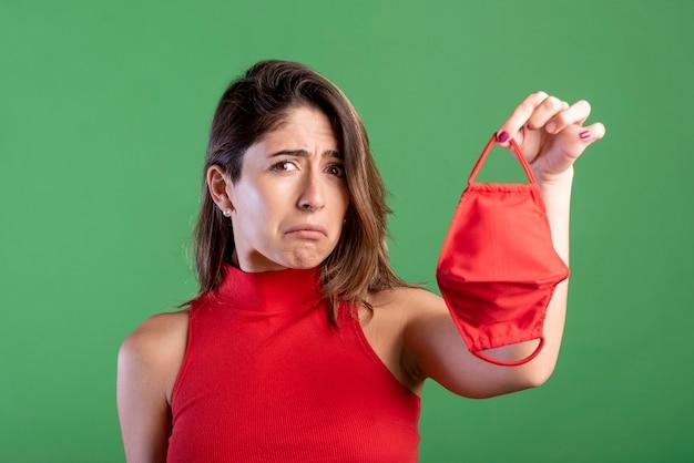 Mulher triste, segurando máscara Foto gratuita